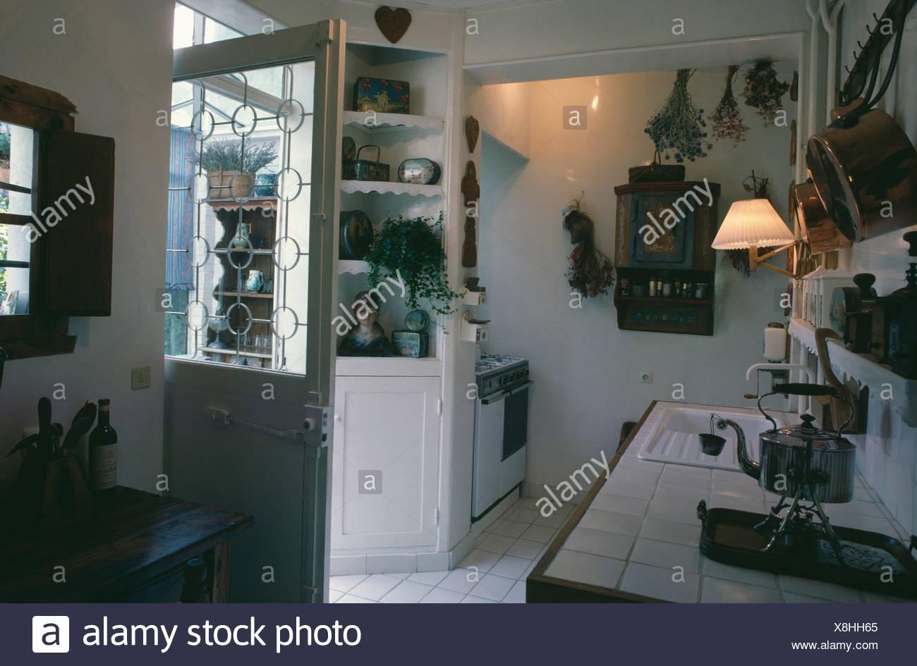 Cucina bianca con parete di luce in piastrelle al di sopra del