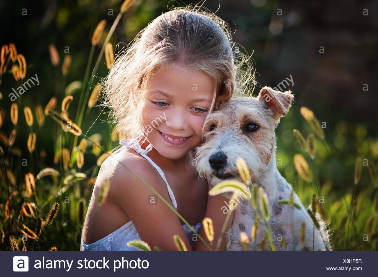 Ritratto di ragazza (6-7) abbracciando il cane Immagini Stock