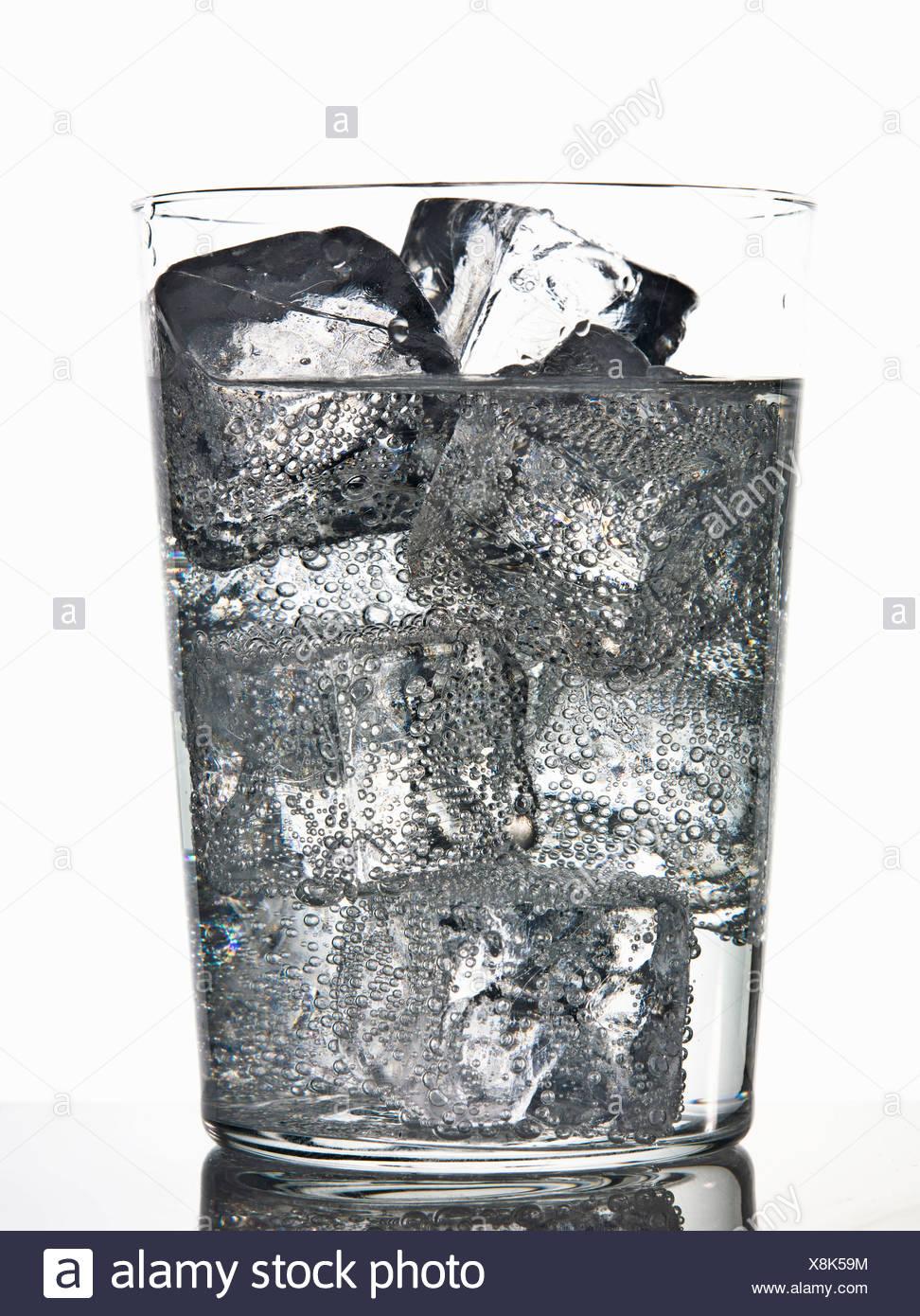 Bicchiere di cubetti di ghiaccio nella bevanda frizzante Foto Stock