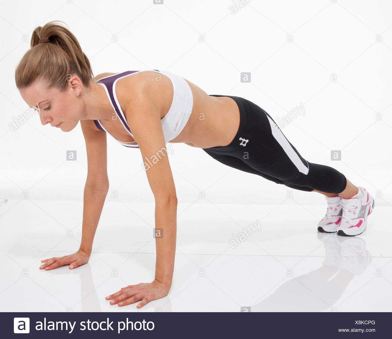 La parte superiore del corpo femmina esercizio capelli biondi legati a coda di cavallo, indossare un giubbotto ritagliata, nero gambali e formatori, eseguendo un Immagini Stock