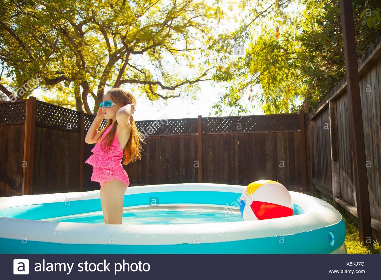 La ragazza di occhiali da nuoto in giardino piscina per