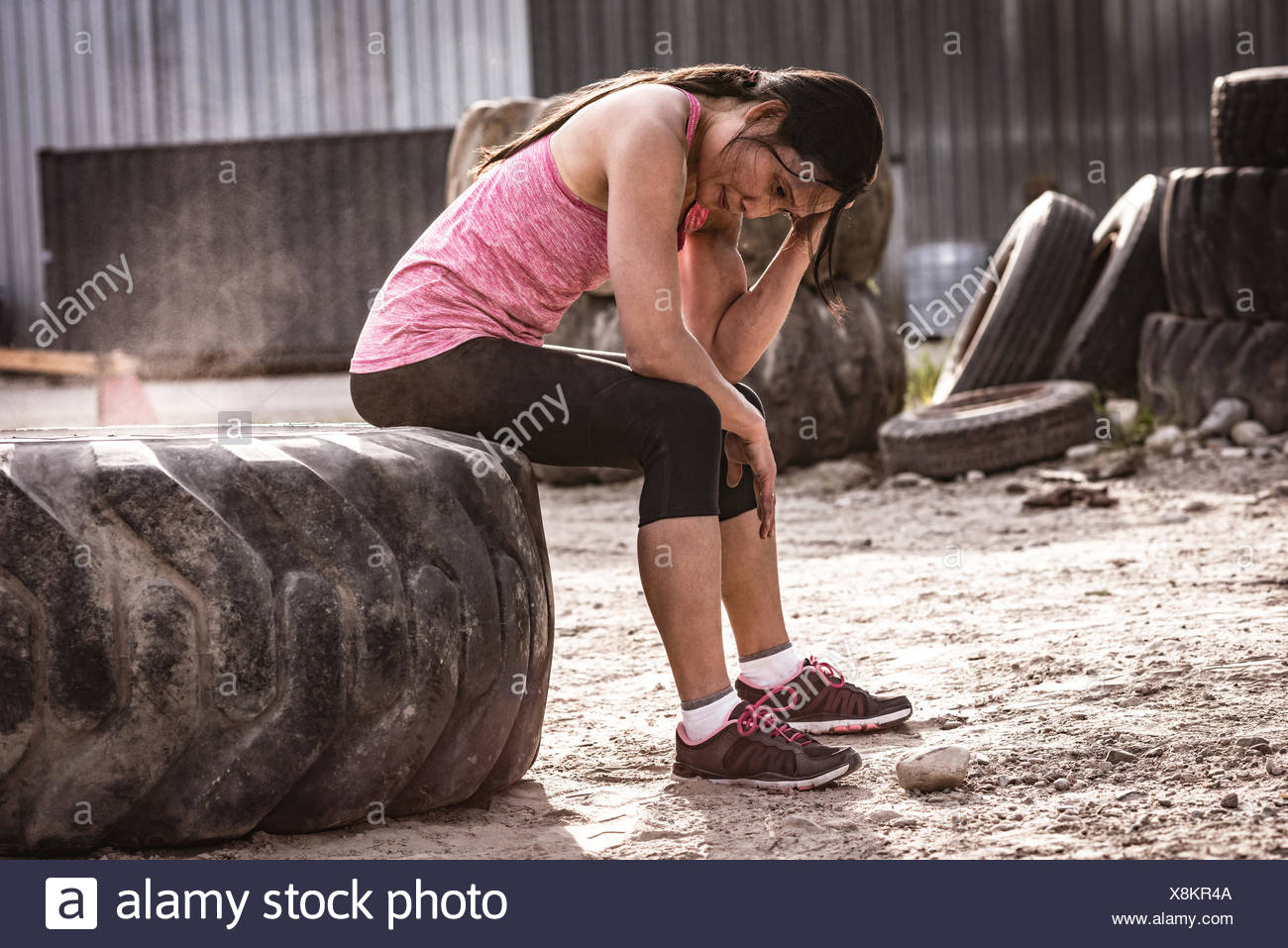 Misura perfetta donna seduta sul pneumatico in una giornata di sole Immagini Stock