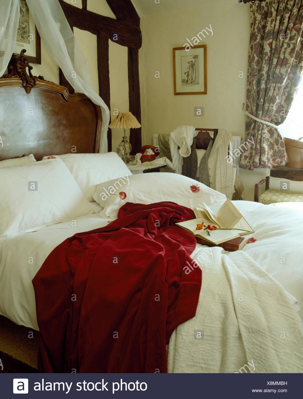 In velluto rosso di gettare e biancheria da letto bianca sul letto ...