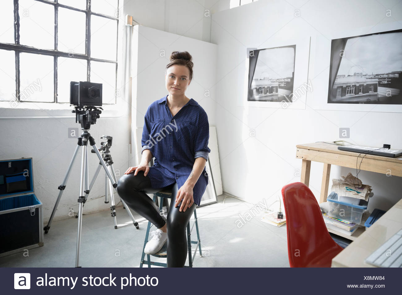 Ritratto femminile fiducioso fotografo seduto su uno sgabello in