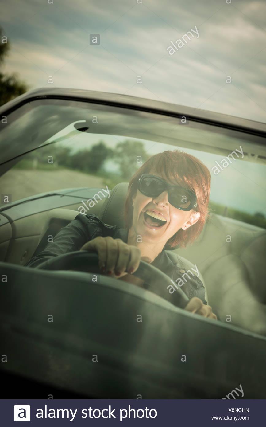 Excited donna godendo la guida la sua autovettura convertibile Immagini Stock