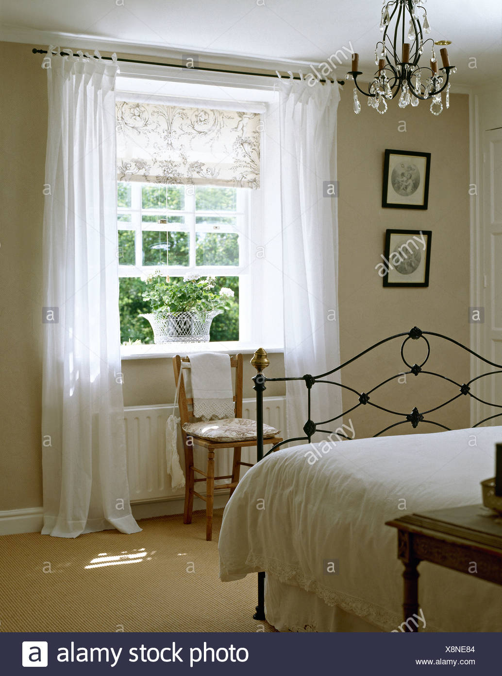 Biancheria da letto bianca sul letto di ferro battuto in ...