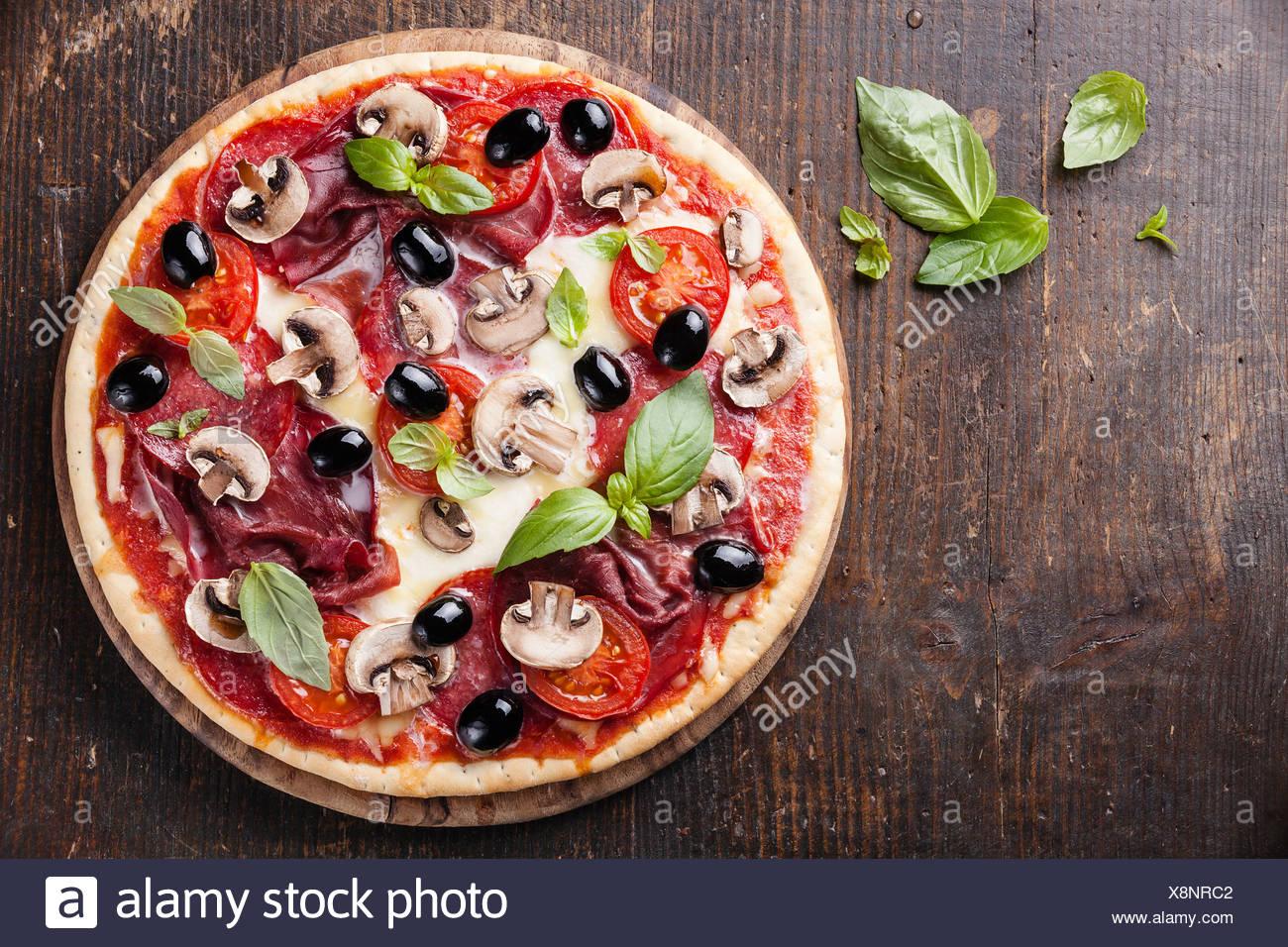 La pizza italiana con salumi, funghi e olive su un tavolo di legno Immagini Stock