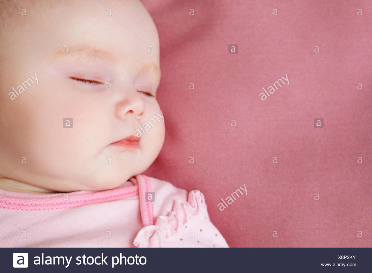 Baby girl dormire nel letto Immagini Stock
