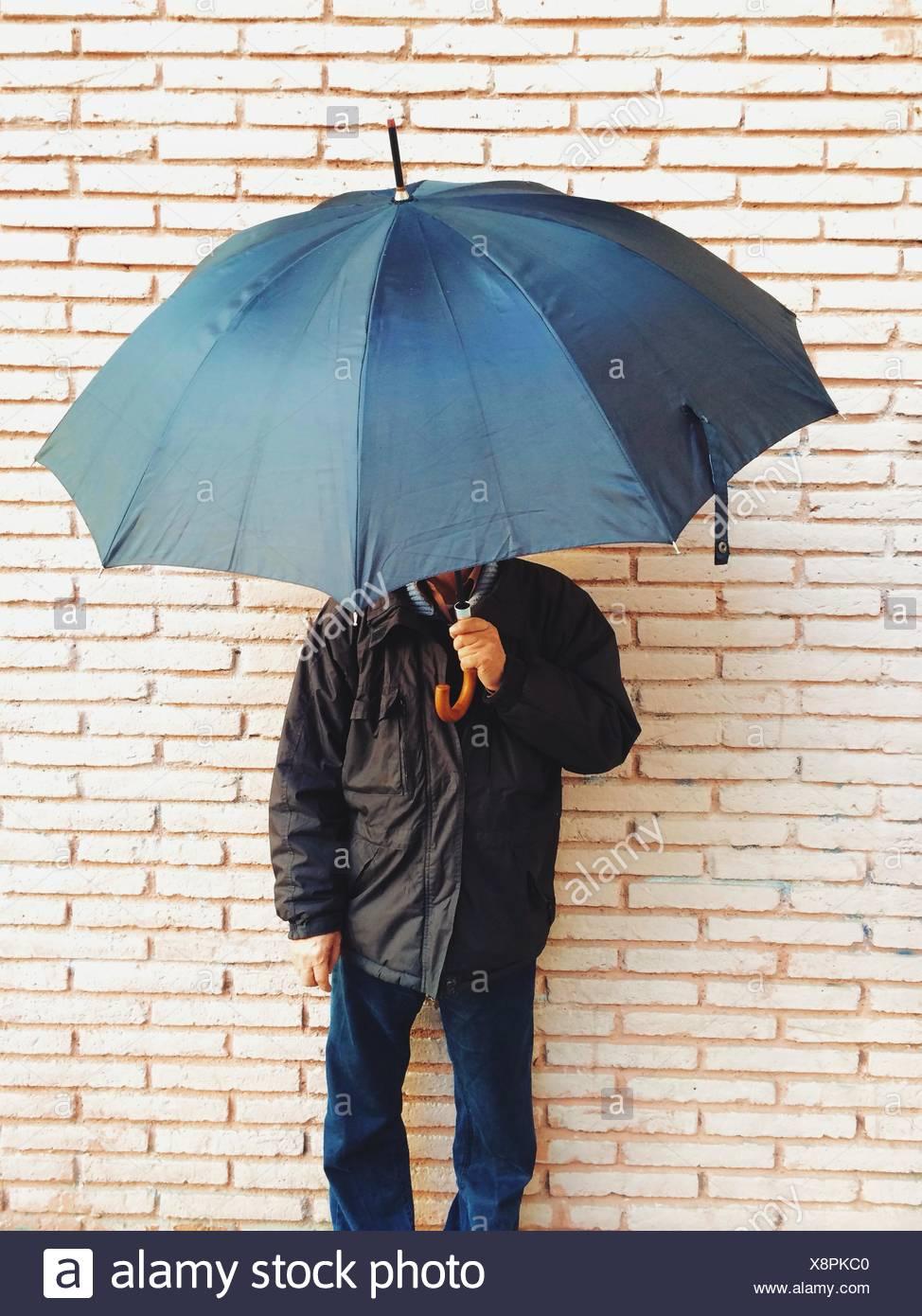 Uomo maturo Holding ombrello contro un muro di mattoni Foto Stock