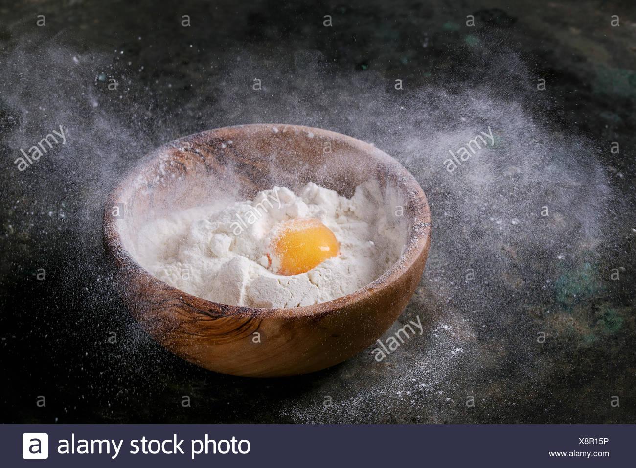 In legno di olivo ciotola con la farina di frumento e di tutto il tuorlo d'uovo su un vecchio metallo scuro dello sfondo. La farina viene spruzzata. Concetto di cottura Immagini Stock