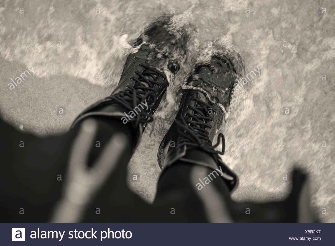 Angolo di Alta Vista della giovane donna nel legare scarponi in mare Immagini Stock