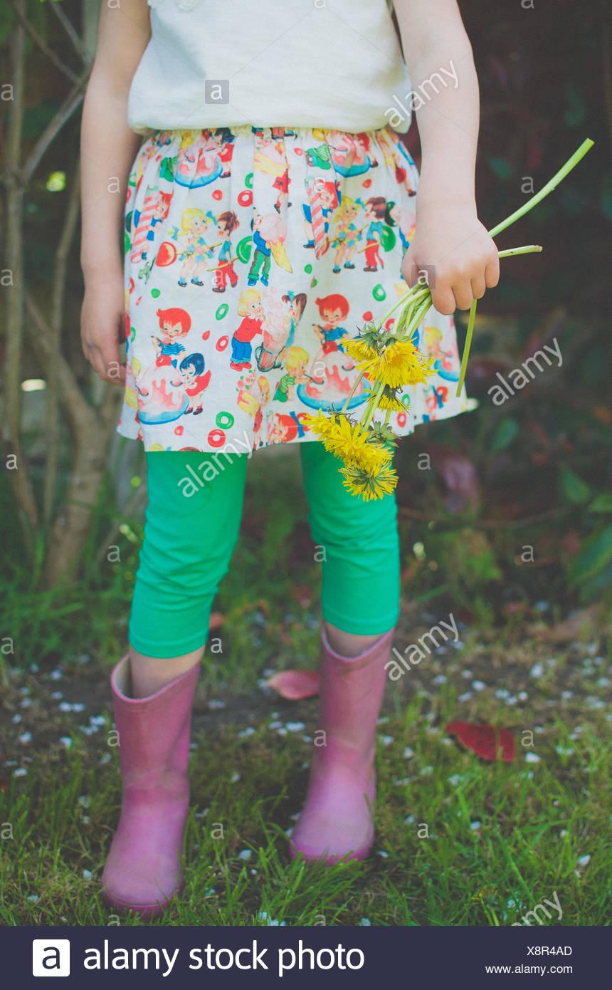 Sezione bassa di una ragazza con i fiori di tarassaco Immagini Stock