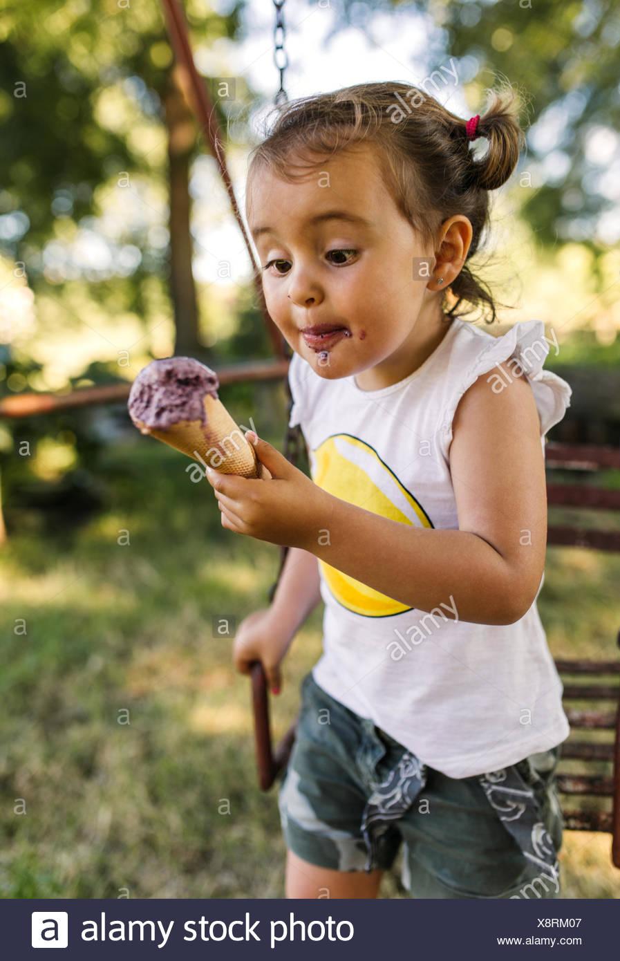 Bambina cercando di mangiare il gelato Immagini Stock