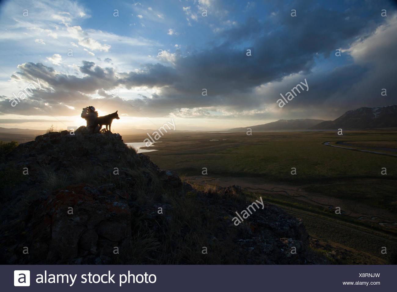 Un wildlife tour guida nella maggior ecosistema di Yellowstone prende il tramonto con il suo cane. Immagini Stock