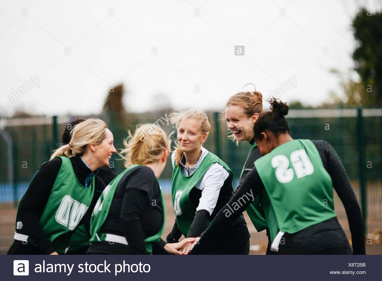 Femmina team netball stringono le mani su netball corte Immagini Stock