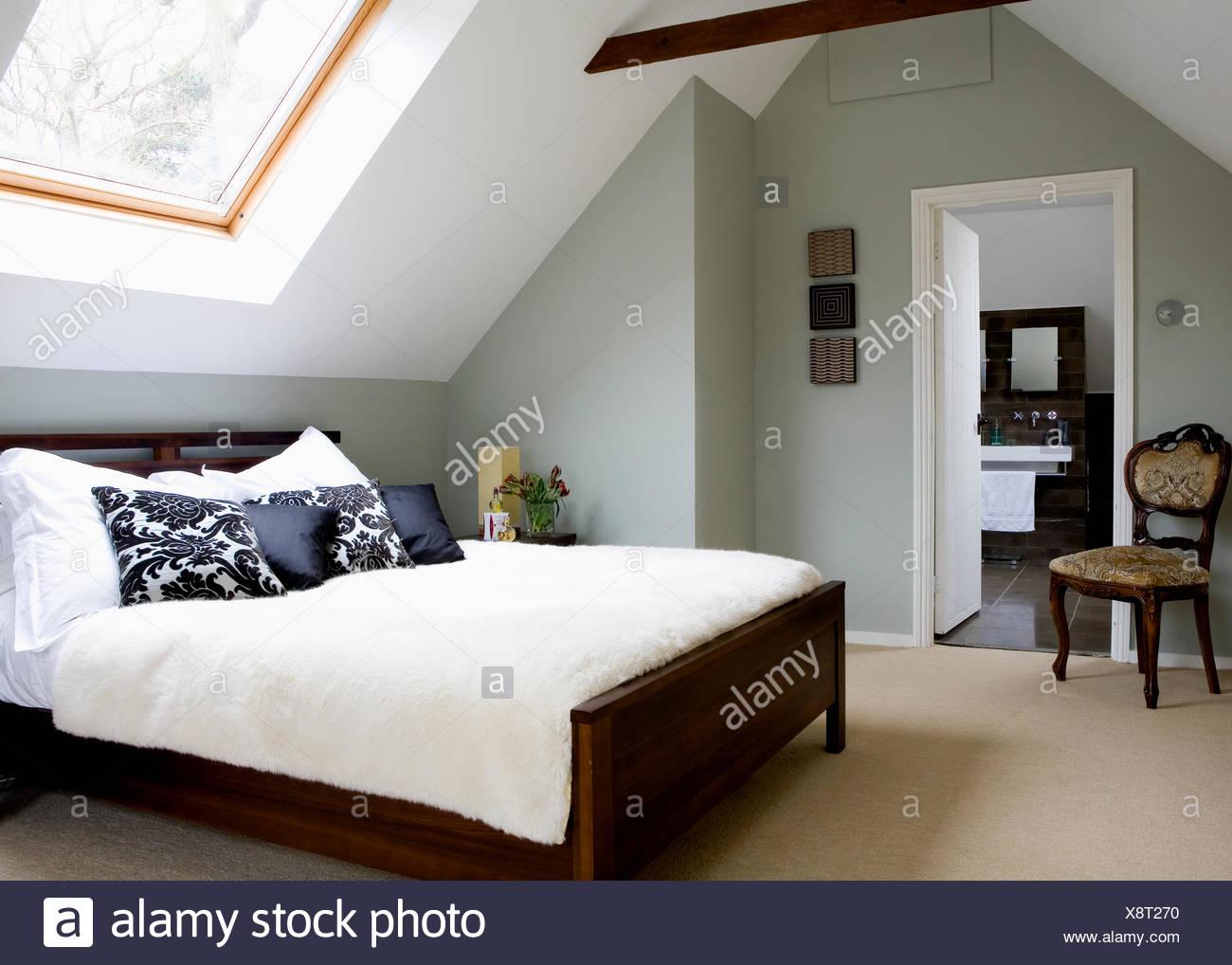 Tappeto color crema e copertura per il letto in mansarda moderna ...