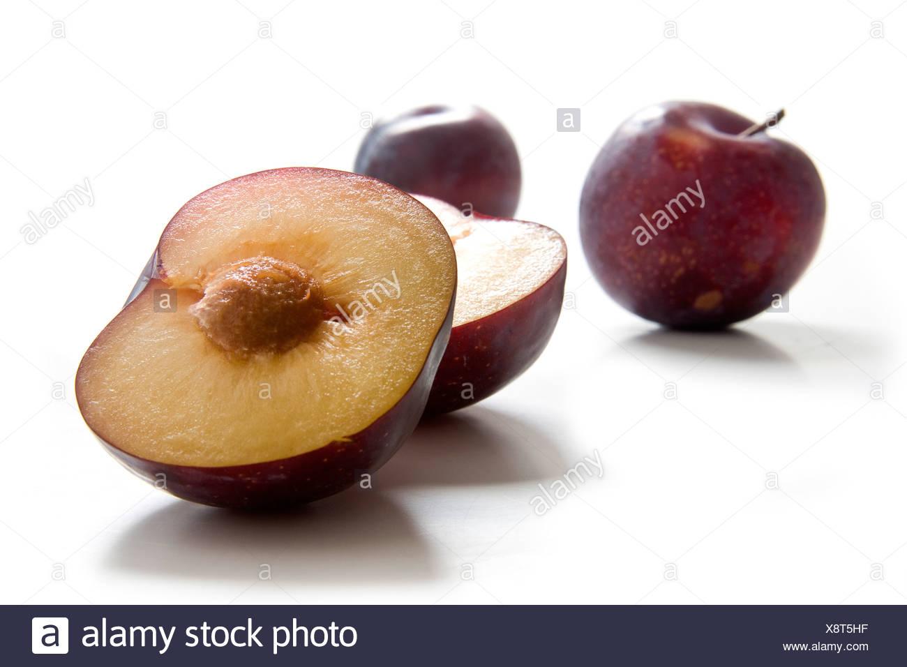 Due interi e metà le prugne, varietà Calita Immagini Stock