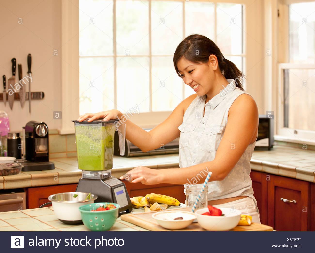 Giovane donna che fa il frullato verde in cucina Immagini Stock
