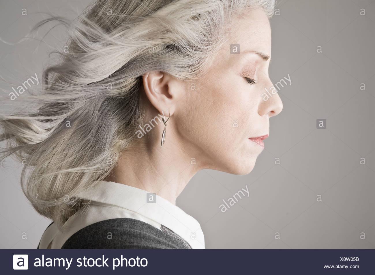 Vista laterale di donna matura con gli occhi chiusi Immagini Stock
