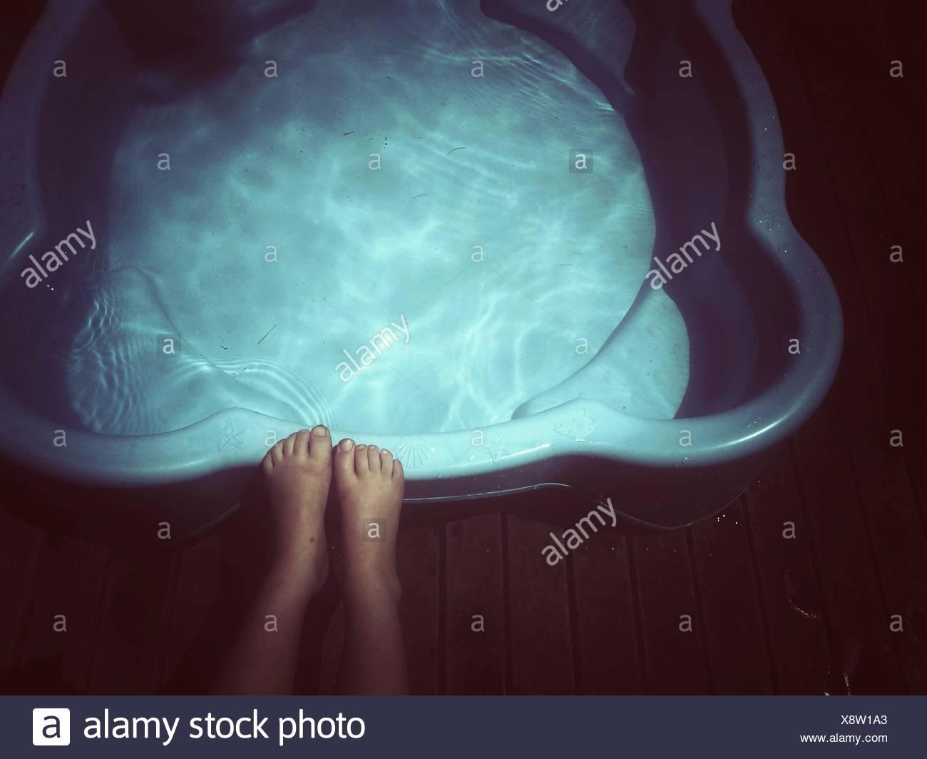 Close-up di una ragazza con i piedi sul bordo di una piscina per i bambini Immagini Stock