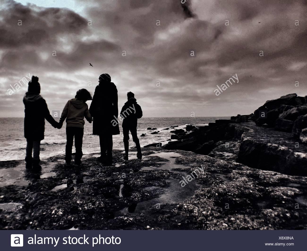 Silhouette di famiglia in piedi alla spiaggia Costa Immagini Stock
