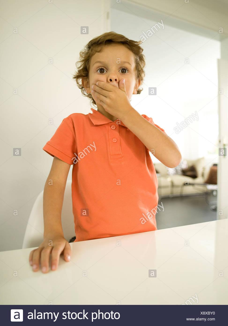 Giovane ragazzo (4-5) che copre la bocca con le mani, ritratto Immagini Stock