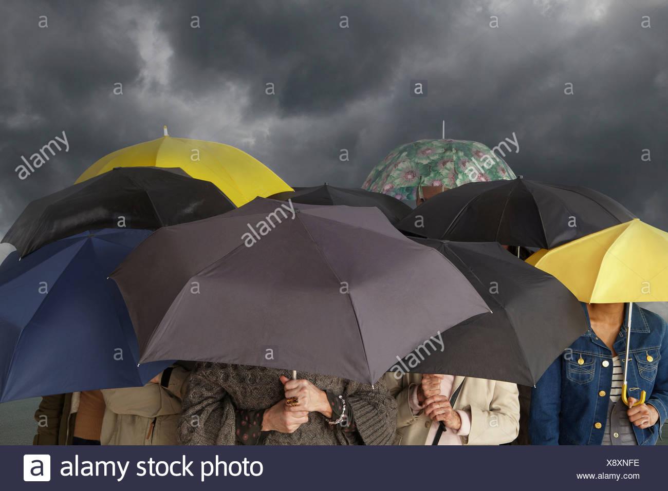 Un gruppo di persone con ombrelloni Immagini Stock