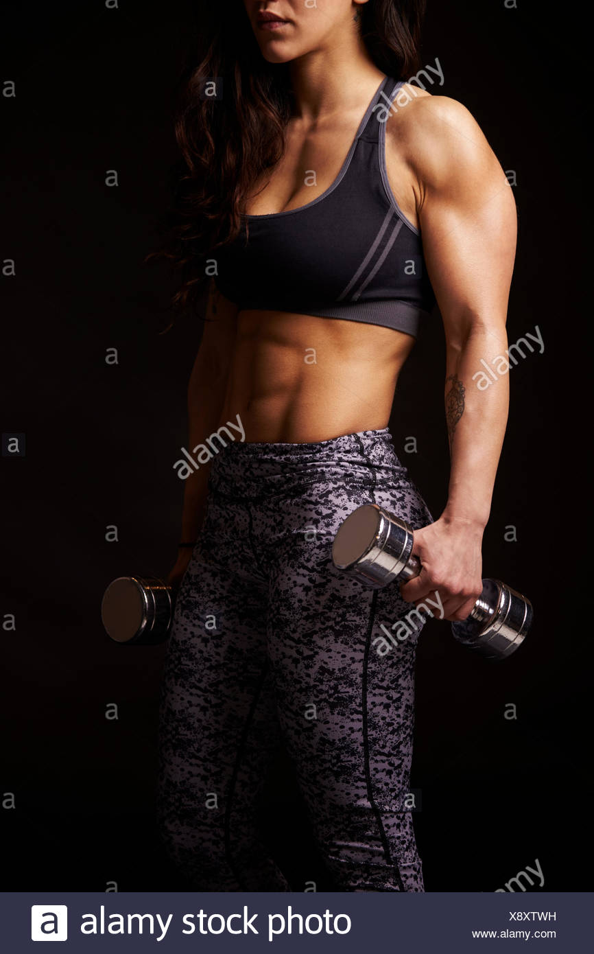 Muscoloso dai capelli scuri donna che lavorano fuori con manubri, raccolto Immagini Stock