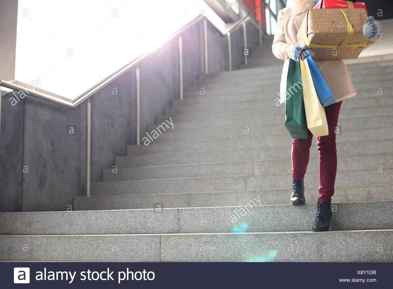 Basso angolo di visione della donna con doni e borse per lo shopping si sta spostando verso il basso le fasi Immagini Stock