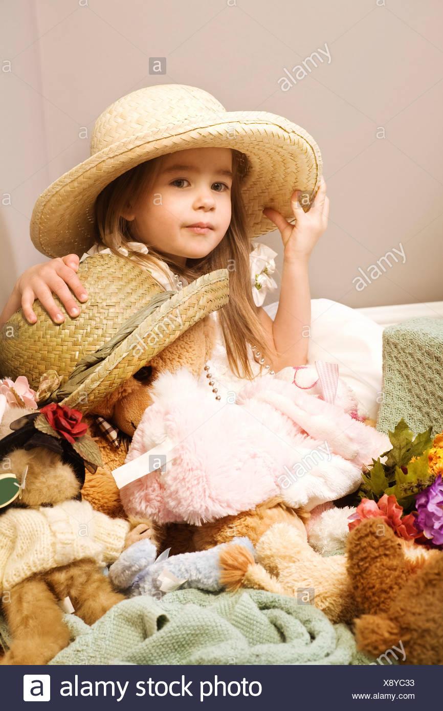 Bambina e orsacchiotto di peluche che indossa cappelli di paglia Immagini  Stock 601b55db3af2