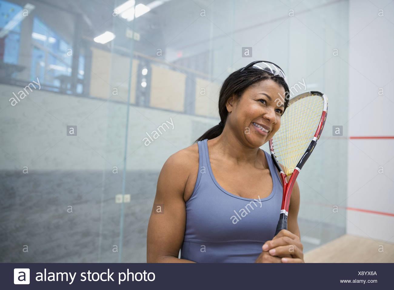 Donna sorridente holding per racchette da squash Immagini Stock