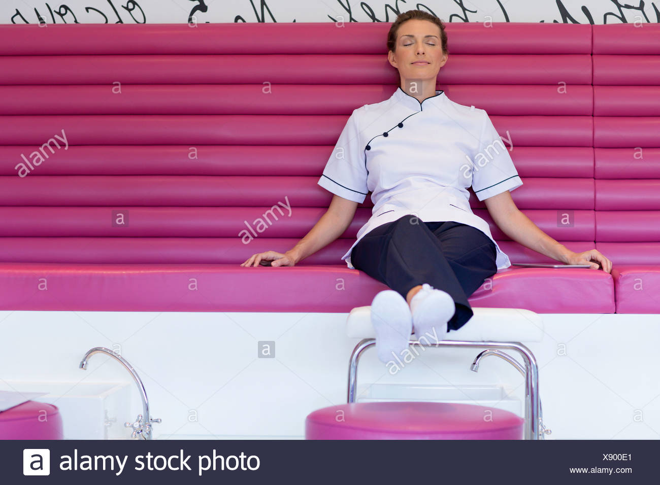 Estetista rilassante con gli occhi chiusi sul banco in salone Immagini Stock