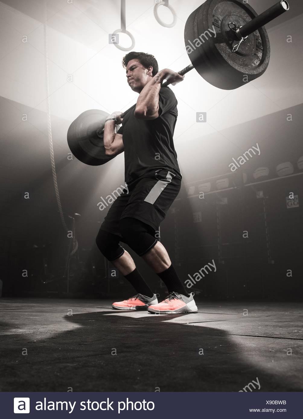 Giovane uomo il sollevamento barbell Immagini Stock