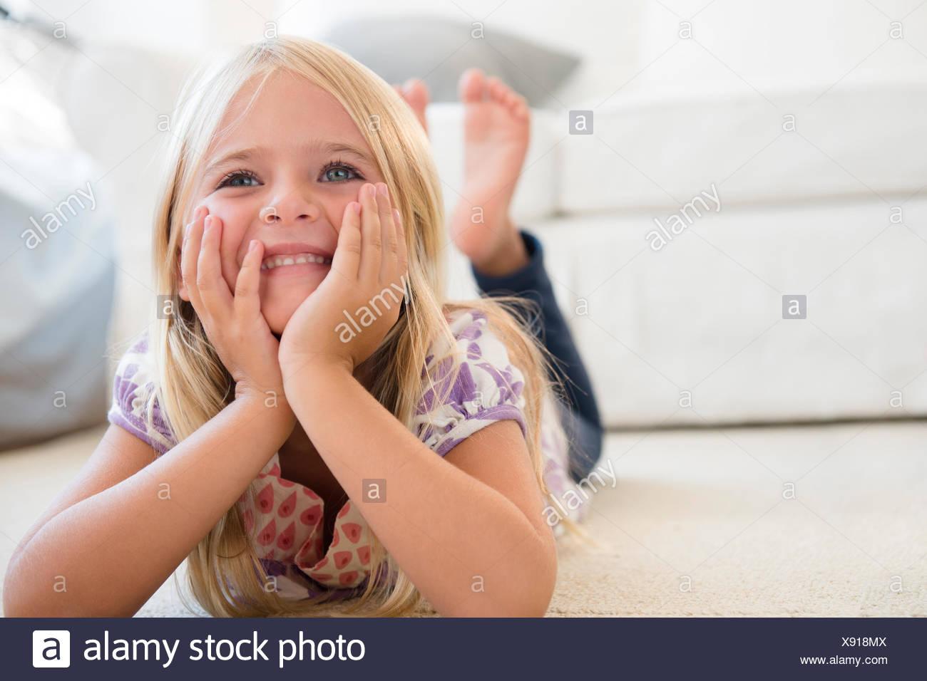 La ragazza (6-7) giacente sul pavimento Immagini Stock