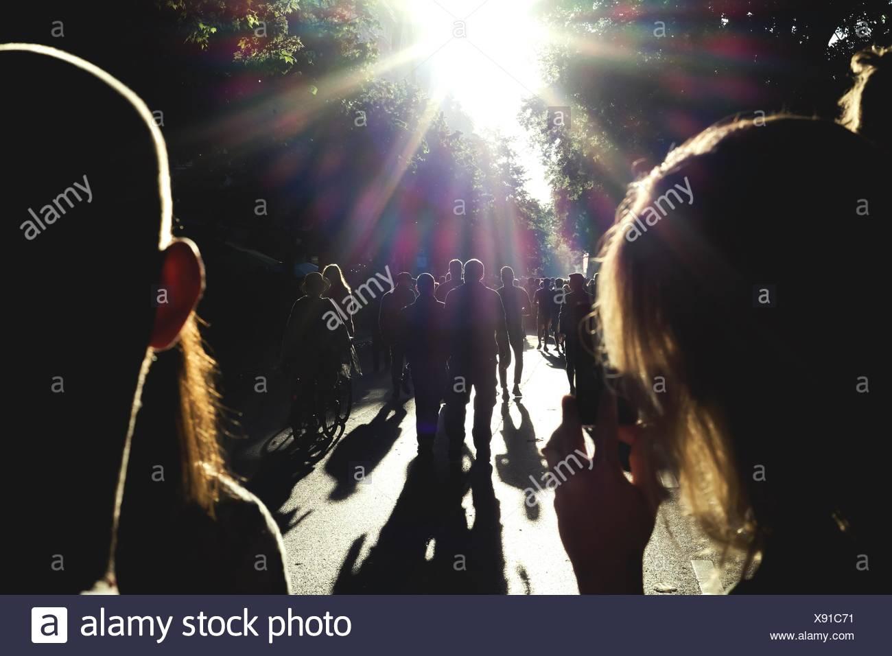 Silhouette gente camminare sulla strada Immagini Stock