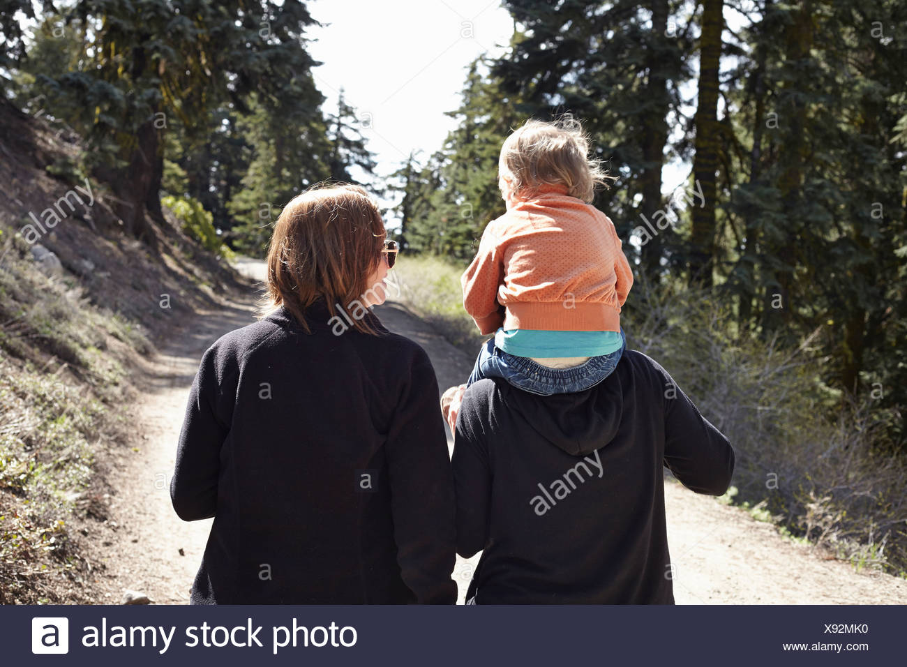 Le donne a camminare attraverso la foresta in Oregon, USA, con il bambino seduto sulle spalle Immagini Stock