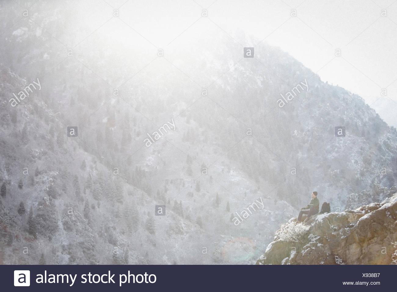 Un uomo, un escursionista in montagna, prendendo un riposo su uno sperone di roccia al di sopra di una valle. Immagini Stock