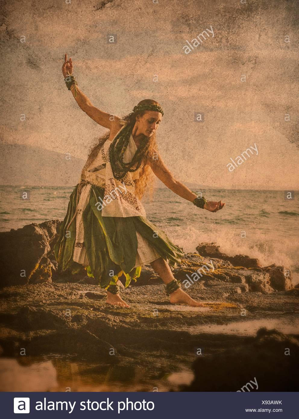 Immagine avanzata di donna hula sulle rocce costiere indossando il costume tradizionale, Maui, Hawaii, STATI UNITI D'AMERICA Immagini Stock