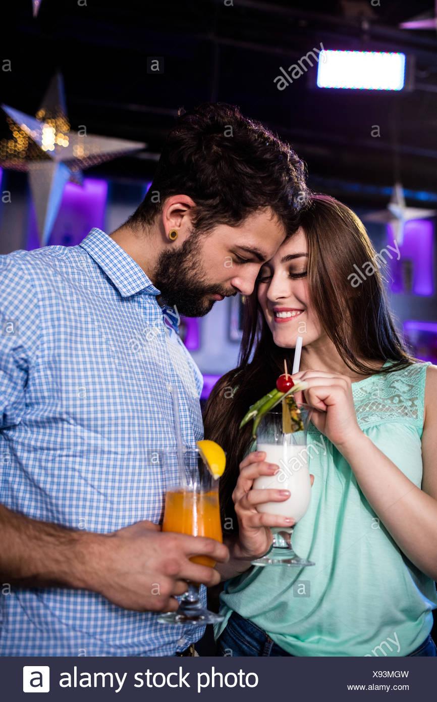 Giovane che abbraccia ogni altra al bancone mentre avente cocktail Immagini Stock