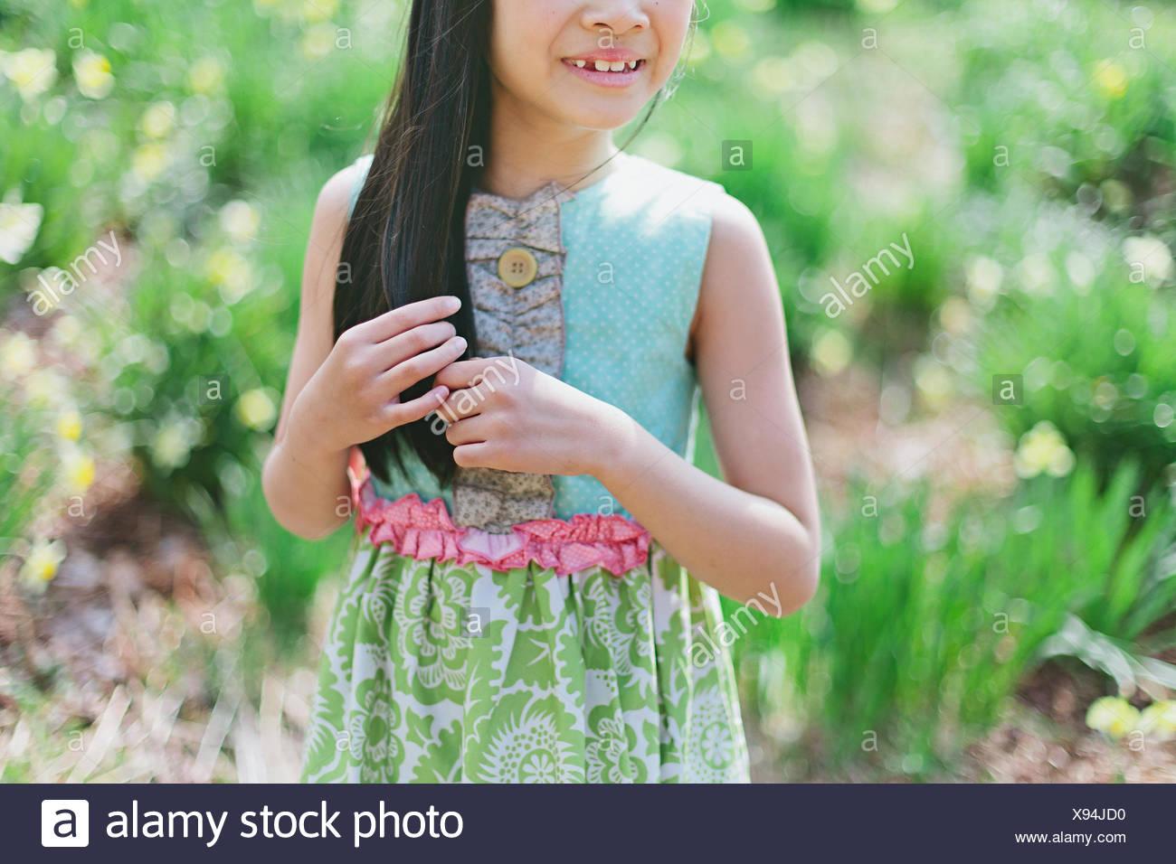 La ragazza (8-9) giocando con i capelli Immagini Stock