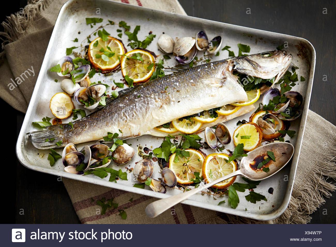 Vassoio da forno con pesce al forno ripiene con limone e erbe aromatiche Immagini Stock