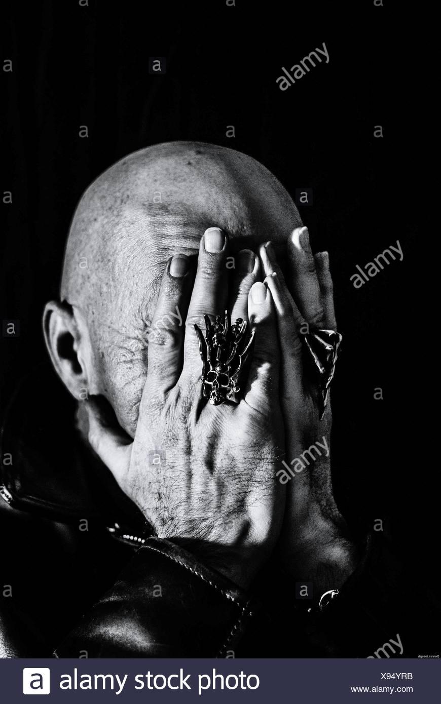Uomo calvo che ricopre la faccia con le mani Immagini Stock