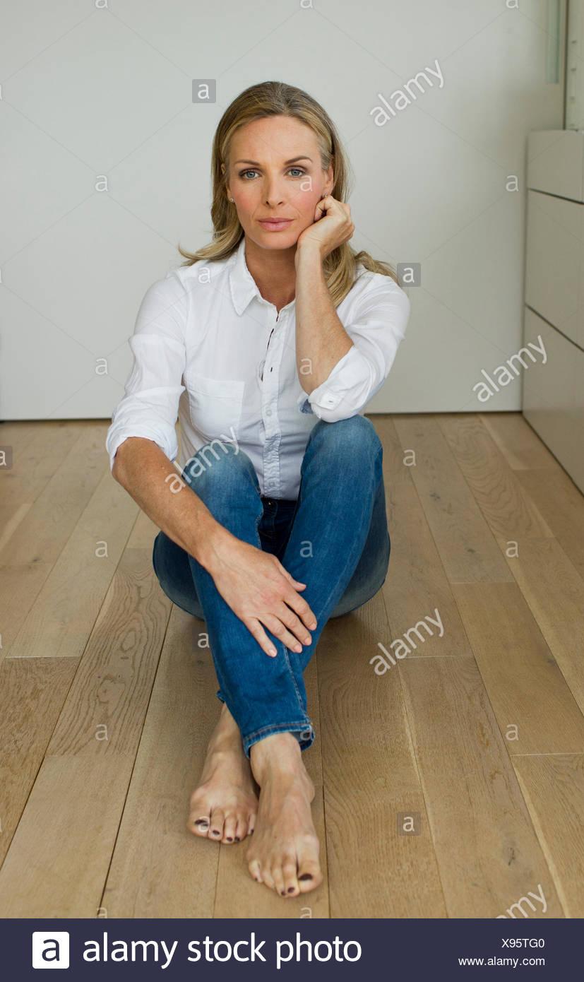 Donna matura seduti sul pavimento in legno, ritratto Immagini Stock
