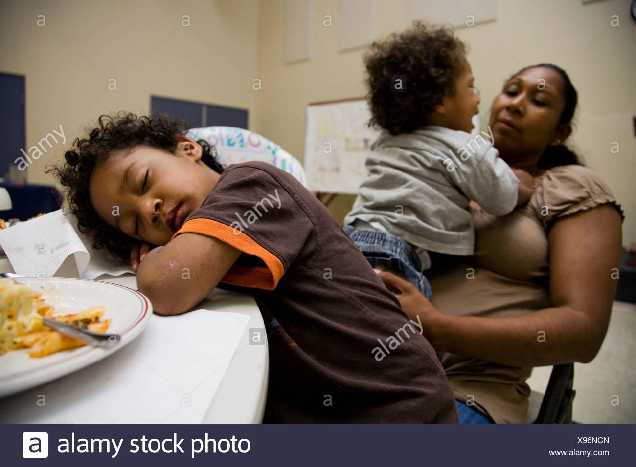 Selena Pina, una casa madre di quattro e i suoi bambini stare in linea per ricevere la cena preparata dai volontari della promessa di famiglia Foto Stock