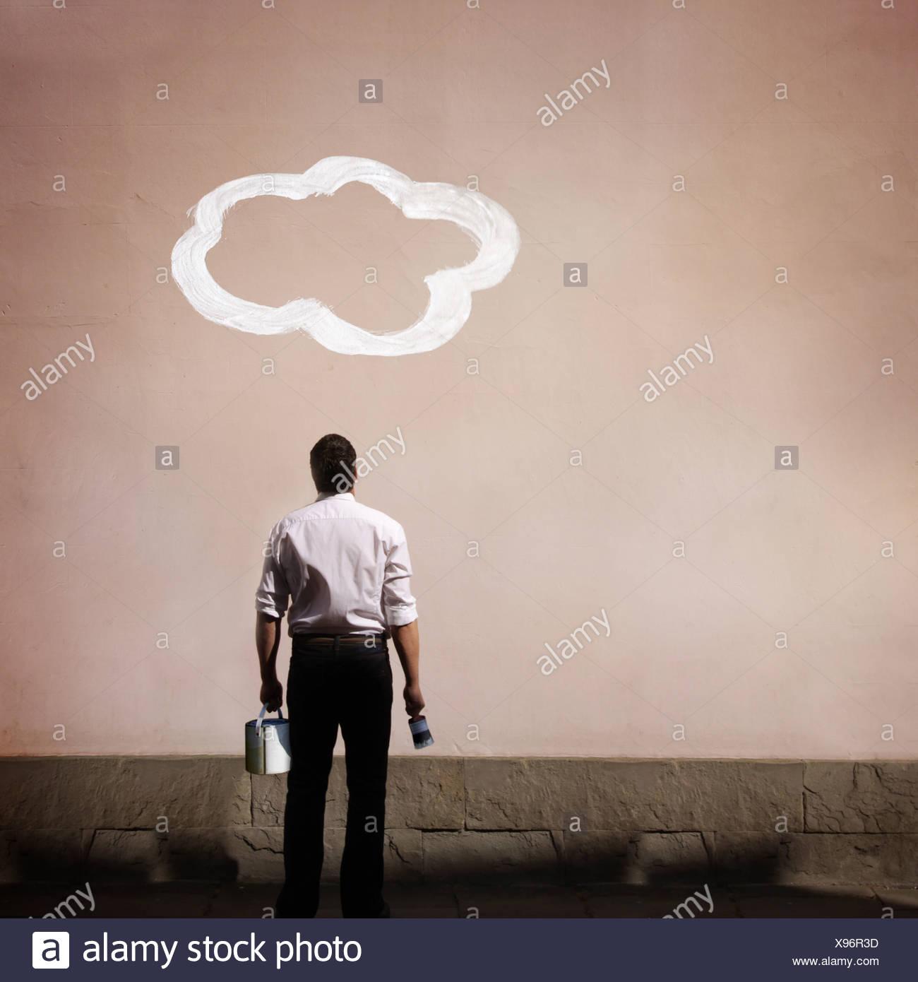 L'uomo con il cloud dipinta sulla parete Immagini Stock