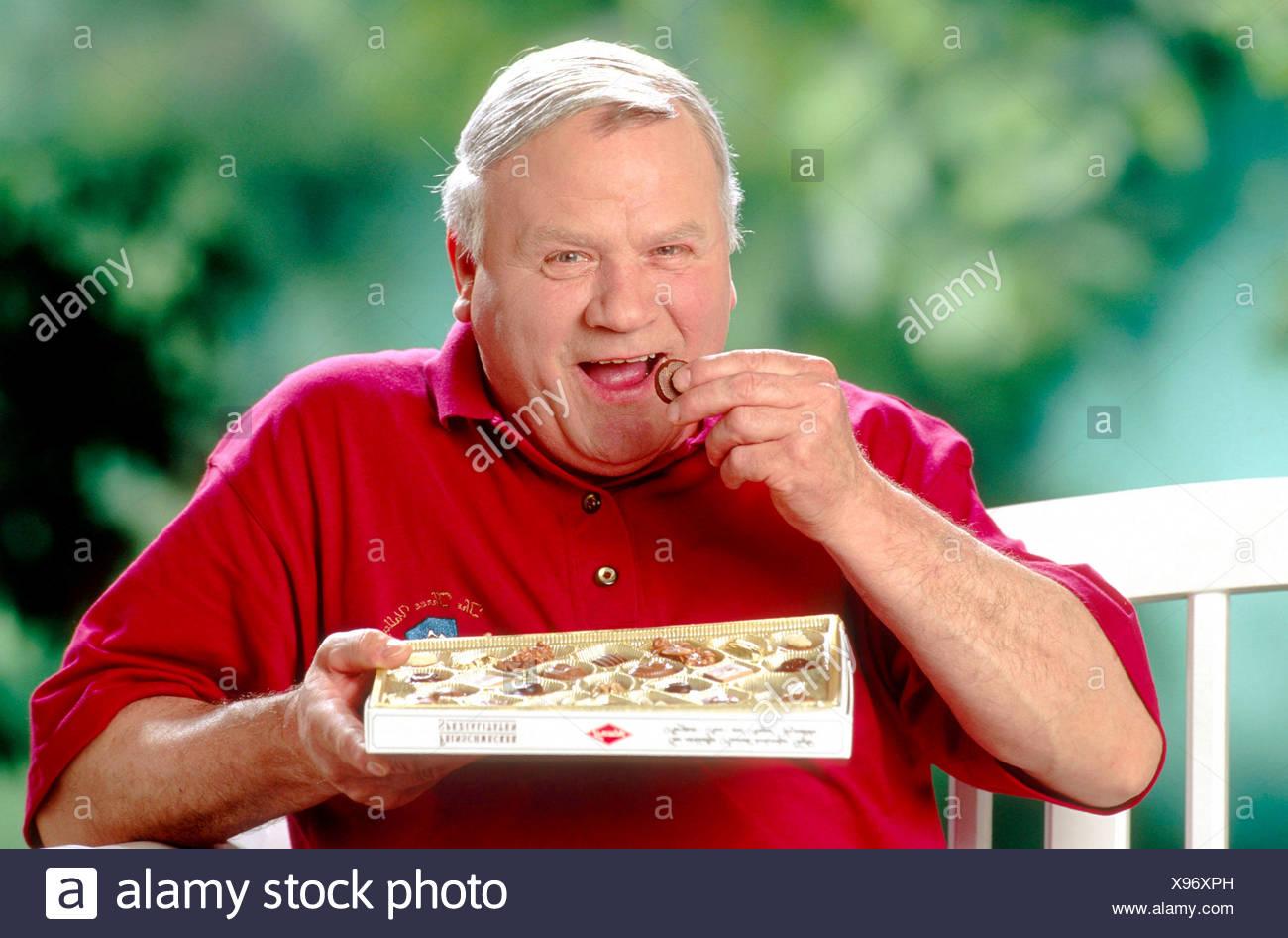 Mann isst Pralinen Immagini Stock