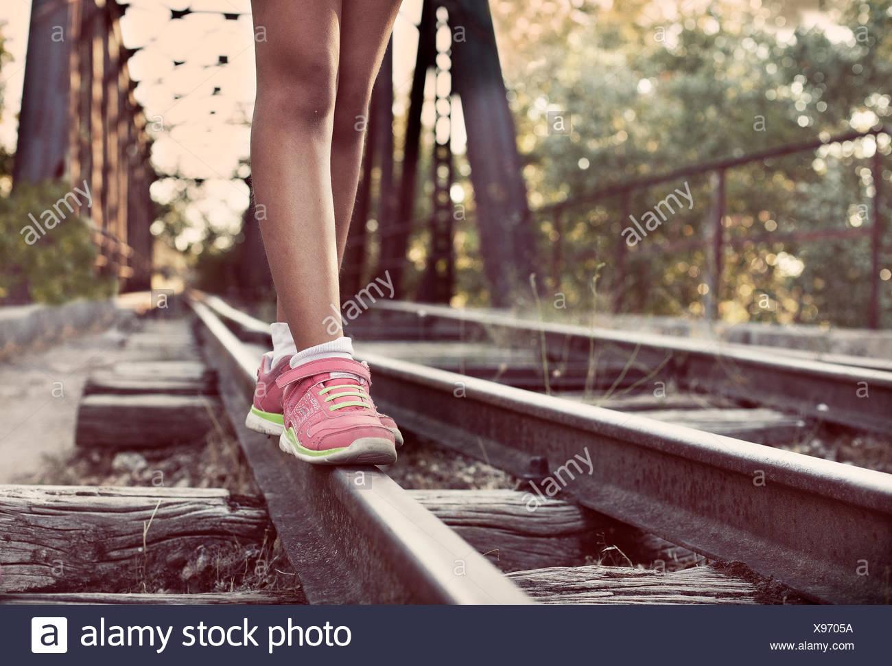 Close-up di donna per le gambe a piedi lungo i binari del treno Immagini Stock