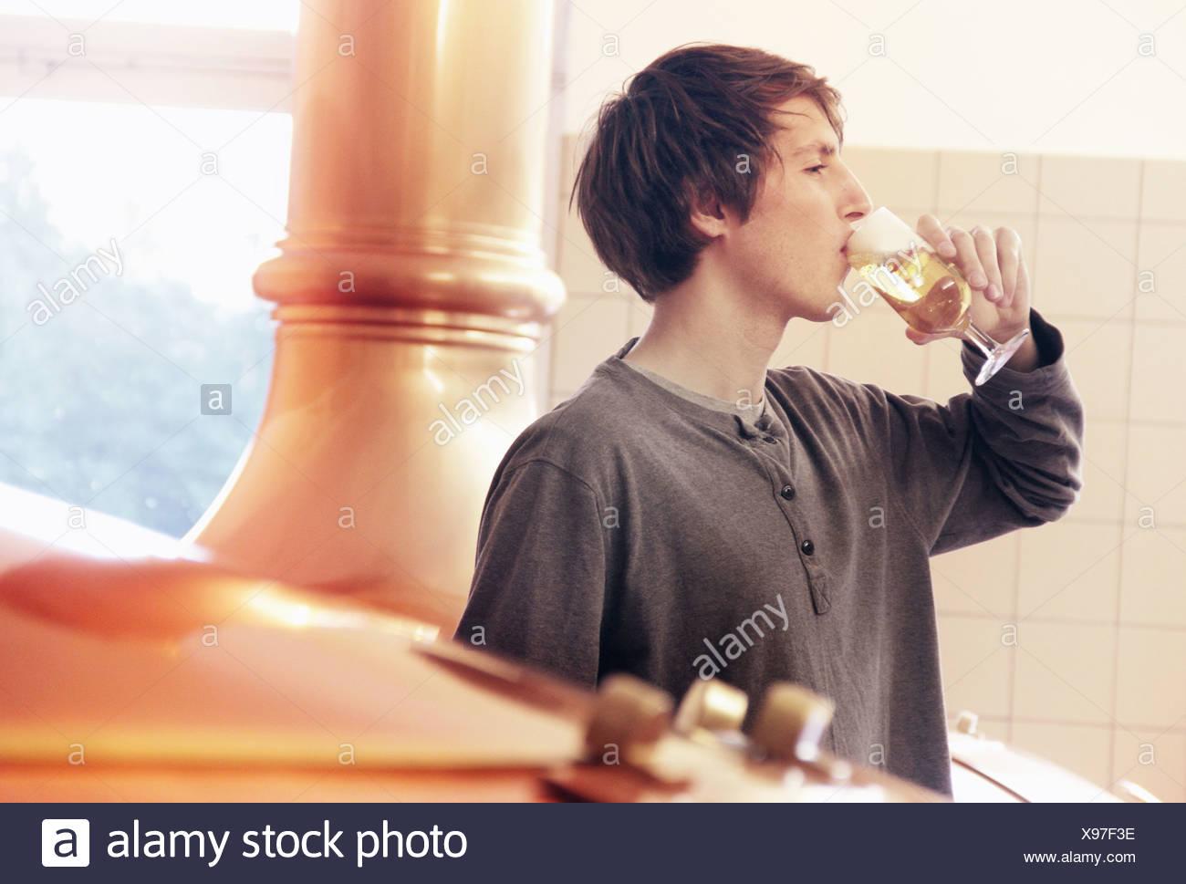 Giovane uomo la degustazione della birra in fabbrica di birra Foto Stock