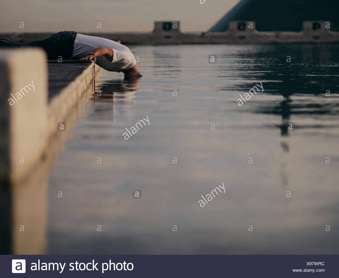 Uomo di mettere la sua testa in acqua Immagini Stock