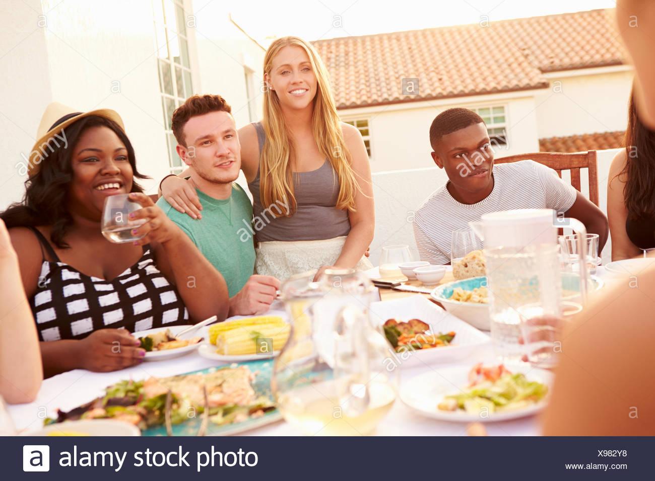 Un gruppo di giovani godendo Outdoor pasto estivo Immagini Stock